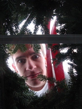 Dylan Prazak peering through Christmas wreath