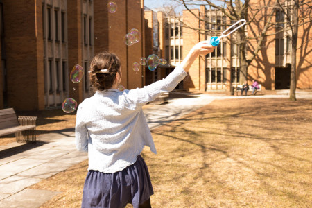 Clara blowing large bubbles in the Massey quad