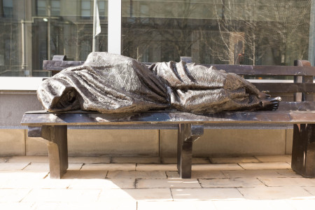 Robed figure sleeping on bench